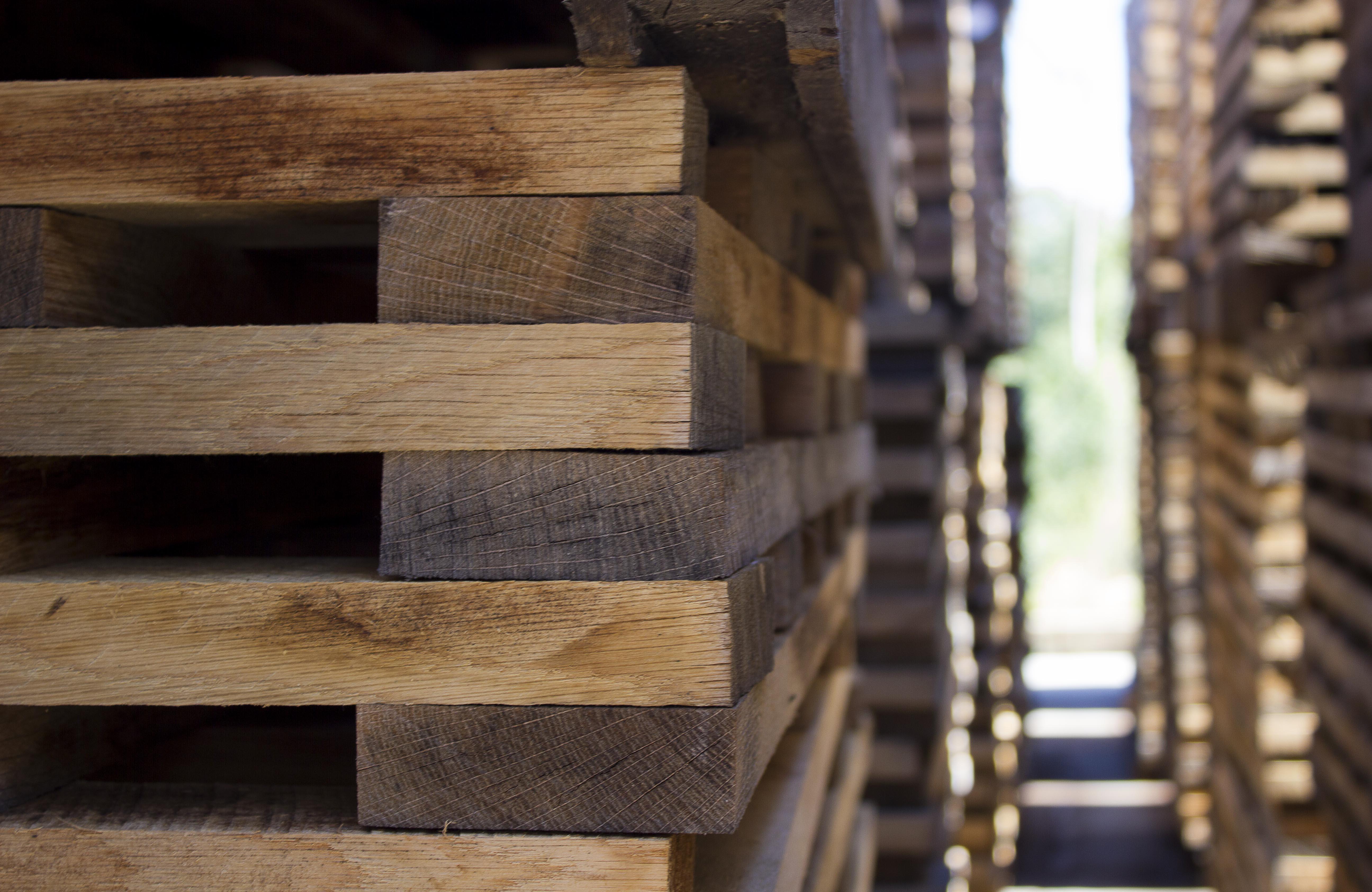 Tablas apiladas en montones preparadas para la fabricación de barricas